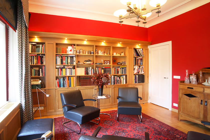 bibliotheek met kast op maakt, rode wand, rood kleed, zwarte stoelen