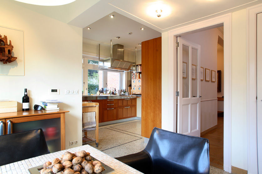 doorkijk wonkamer naar keuken, zwarte stoel, hout, tafel