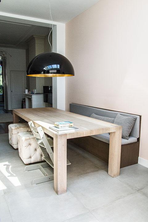 eethoek met houten tafel en stoelen, en bank tegen de muur