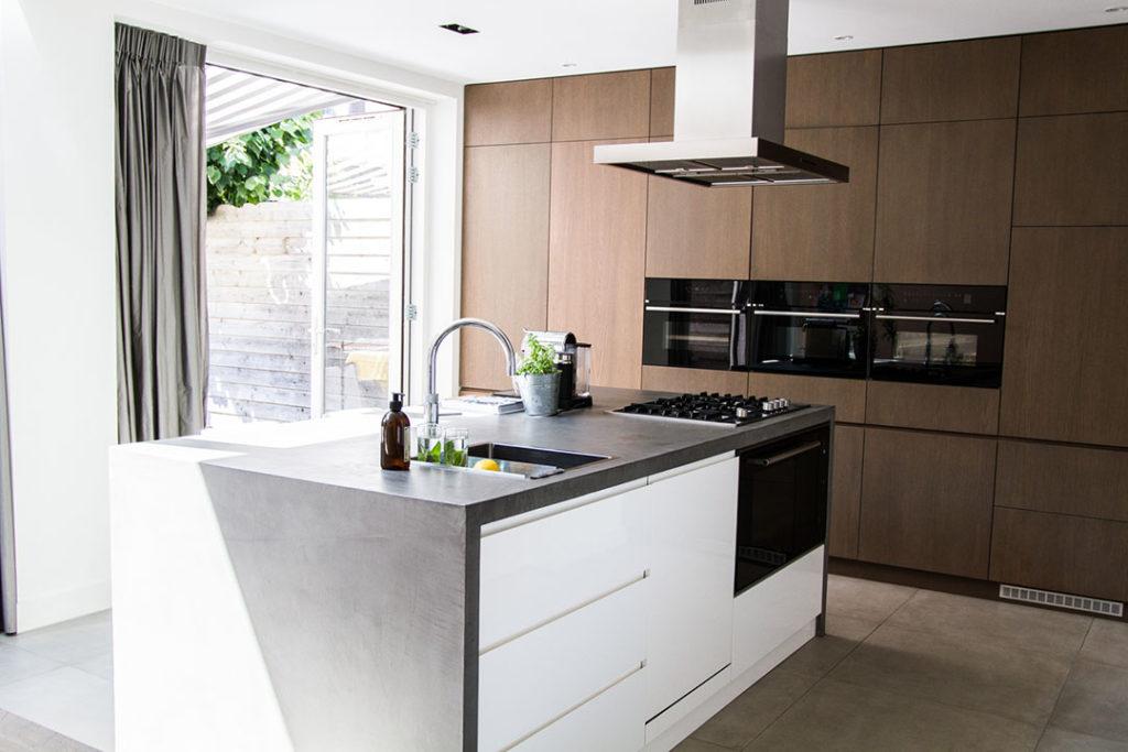 keukenblok met houten wand met donker blad en witte lades, inbouwapparatuur