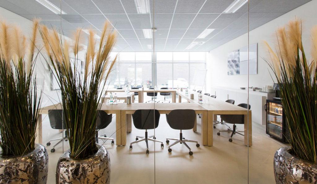 tafels op maat, zwarte stoelen op wielen, planten, interieurontwerp