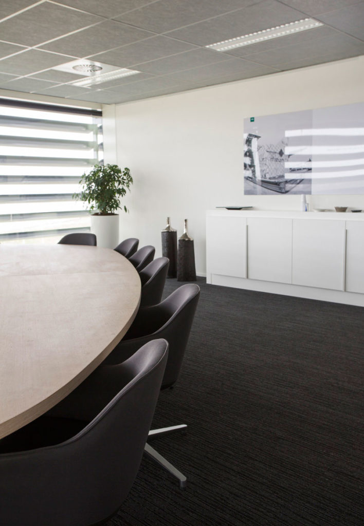 vergaderruimte met houten tafel en witte kast op maat