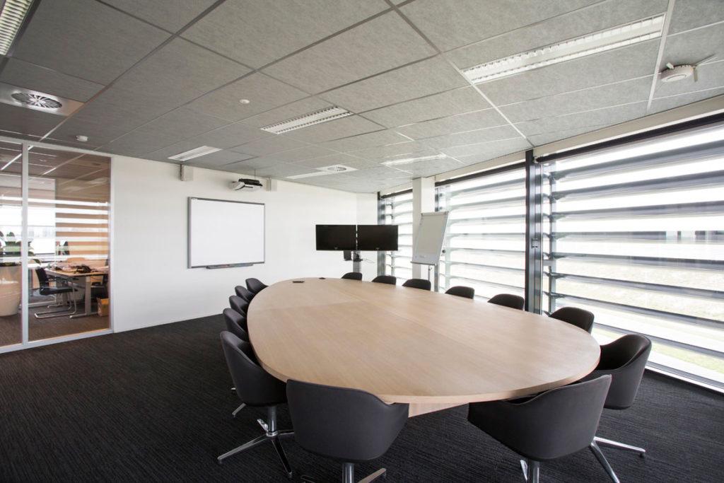 vergaderruimte met tafel op maat, hout, donkere stoelen, donkere vloerbedekking